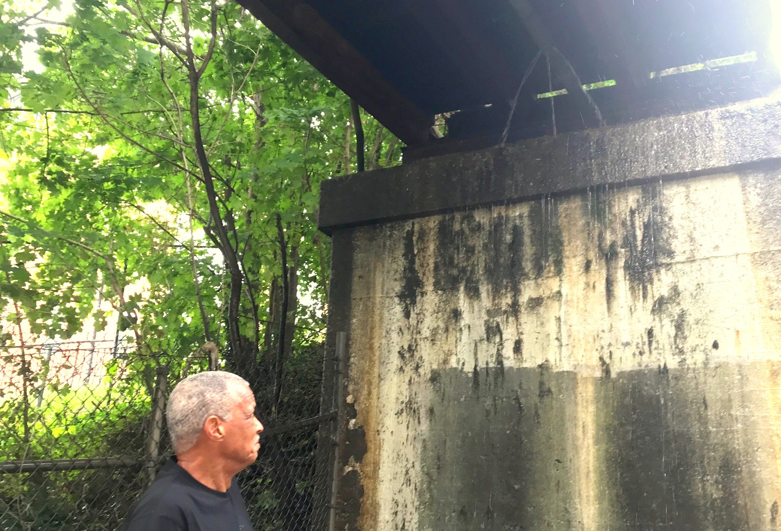 Charles Levi looks up at the water that running continuously off of the CSX bridge, which he is sure is connected to the dirty water that comes into Mount Hebron Baptist Church located about 100 feet from the bridge. (Both Mark Reutter)