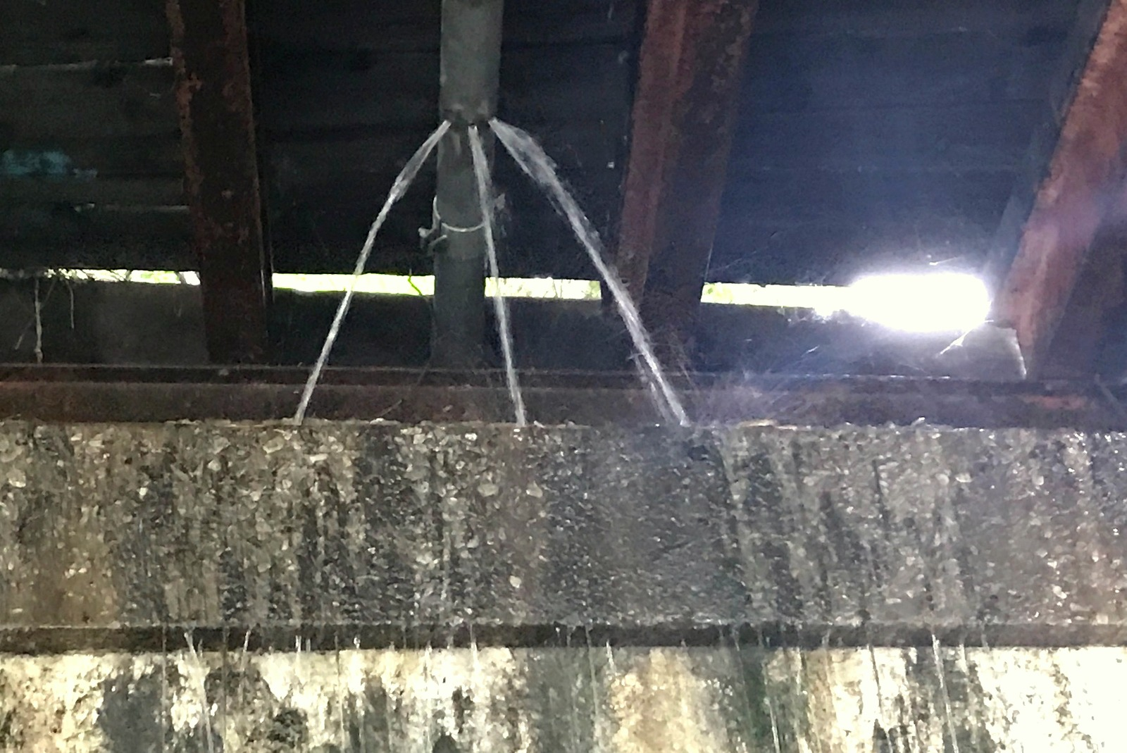 This pipe on the CSX bridge has been broken for at least 18 months, according to two Coppin State employees, and its emergency phone number does not connect to AT&T, the apparent owner of the cable line. (Mark Reutter)