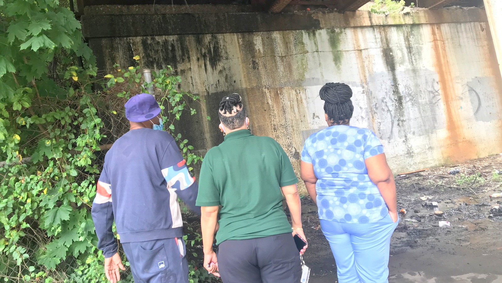 Curtis Brown and two passers-by look at the water cascading down the concrete abutments of the CSX bridge over North Avenue. (Mark Reutter)